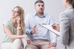 Furious man during couples therapy. Bored women and furious men trying to save marriage during couples therapy Stock Photos