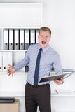 Furious man is holding a file in the office Stock Photos