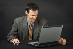 Furious man looks at laptop screen Stock Images