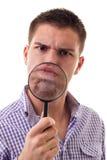 Furious man through Magnifying glass Royalty Free Stock Photos