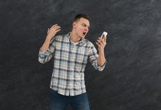 Furious man shouting at his mobile phone. Young angry aggressive man shouting at his mobile phone, gray studio background, copy space Stock Photo