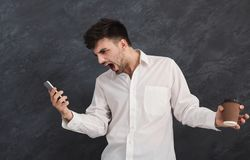 Furious man shouting at his mobile phone. Young angry aggressive man shouting at his mobile phone and holding coffee cup, black studio background, copy space Stock Photos