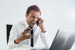 Furious man shouting on phone. Furious african american businessman sitting at office desk with laptop shouting at interlocutor over the phone. Concept of stress Royalty Free Stock Photo