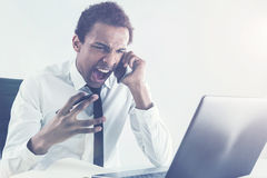 Furious man shouting on smartphone. Furious african american businessman sitting at an office desk with laptop shouting at interlocutor over the phone. Toned Stock Photo