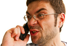 Furious Man Talking By Phone. Portrait of a displeased furious man, he is talking by phone and screaming, isolated on white background Royalty Free Stock Photo