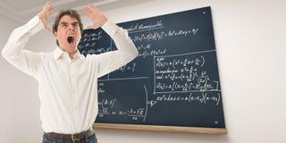 Furious maths teacher. Angry teacher in a mathematics class royalty free stock photos
