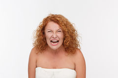 Furious mature woman. Mature Caucasian woman yelling with angry expression. Picture of furious mature woman posing isolated on white in studio Royalty Free Stock Image