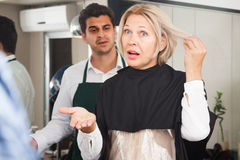 Furious mature woman screaming on hairdresser as hair cut badly. Furious mature women screaming on hairdresser as hair cut badly at the hairdresser Stock Image