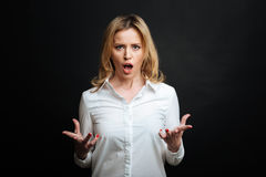 Furious mature woman yelling in the black colored studio Stock Photo