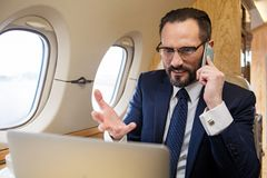 Furious middle aged male having unpleasant conversation. Things go worse. Portrait of dissatisfied diplomat in private airplane talking by mobile phone and Royalty Free Stock Photos
