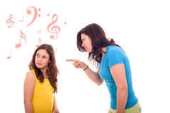 Furious mother. Yelling at her daughter that pretends listening music Stock Photo