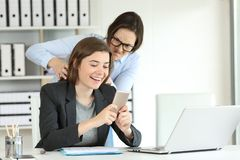 Furious office worker angry with her lazy colleague. Trying to strangle stock image
