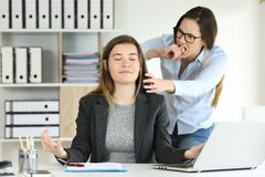 Furious office worker trying to kill her colleague. Furious office worker trying to kill her lazy colleague who is wasting time practicing yoga exercises stock photos