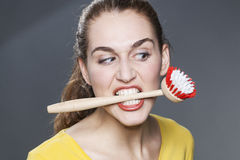 Furious 20s girl with dish brush in teeth for cleaning and washing refusal Stock Image