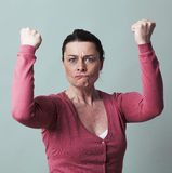 Furious 40s woman flexing her muscles up for female independence Royalty Free Stock Image