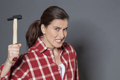 Furious 30s woman holding hammer for aggression or self-defense Royalty Free Stock Photos