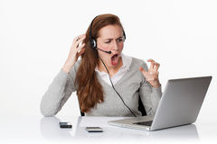 Furious 20s working woman under shock with headset and computer Royalty Free Stock Image