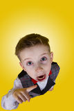 Furious Screaming little boy. Pointing with finger over yellow background.Family Imitation Stock Photos
