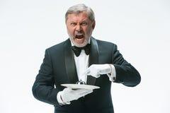 Senior waiter holding bell Stock Images
