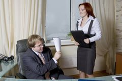 Furious secretary going to beat boss. Royalty Free Stock Photography