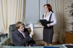 Furious secretary trying to beat her boss Stock Images