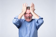 Furious senior man holding his head in hands and screaming. Negative facial emotion royalty free stock image