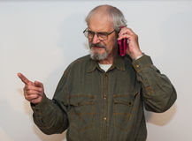 Furious senior man talking on the phone. Furious senior man talking on the phone on white background Stock Photos