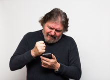 Furious senior man. Furious senior man trying to text on a cell phone Stock Photography