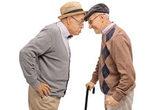 Furious seniors pushing their heads against each other. Isolated on white background Royalty Free Stock Images