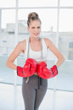Furious sporty blonde wearing red boxing gloves Royalty Free Stock Image