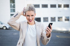 Furious stylish businesswoman holding her phone Royalty Free Stock Image