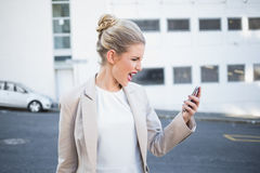 Furious stylish businesswoman shouting at her phone. Outdoors on urban background Royalty Free Stock Photography