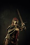 Furious warrior. Powerful furious amazon with two-handed sword over dark background royalty free stock image