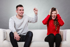 Furious wife and happy husband. Disagreement. Furious angry upset women and happy joyful husband sitting on sofa at home. Man laughing at woman. Boyfriend Stock Photography
