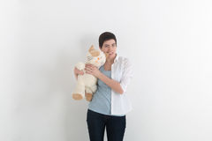 Furious woman bite her plush toy cat for ear, gray studio background. Funny situation.  Royalty Free Stock Image