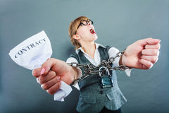 Furious woman with chained hands and contract Royalty Free Stock Image