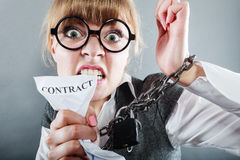 Furious woman with chained hands and contract. Business and stress concept. Furious businesswoman in glasses with chained hands holding contract grunge Stock Photography