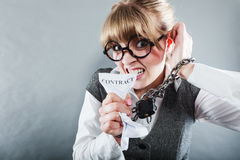 Furious woman with chained hands and contract. Business and stress concept. Furious businesswoman in glasses with chained hands holding contract grunge Royalty Free Stock Image