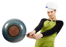 Furious woman cook hitting with the frying pan Royalty Free Stock Photography