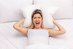Furious woman covering ears with pillow Royalty Free Stock Photos