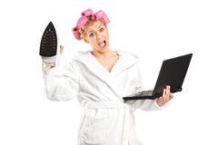 Furious woman holding an iron and a laptop Royalty Free Stock Photos