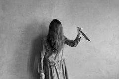 Furious woman with long hair and a knife Royalty Free Stock Photography