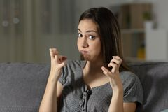 Furious woman looking at camera in the night. Sitting on a couch in the living room at home Stock Photos
