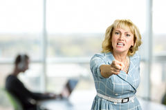 Furious woman, office window background. Pointing angry businesswoman holding somebody responsible. Irritated mature woman shouting and pointing with index Stock Images