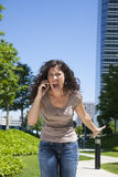 Furious woman shouting phone. Portrait of angry woman shouting to mobile at street Royalty Free Stock Image
