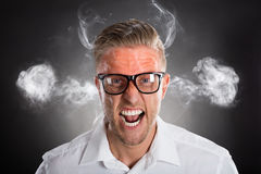 Furious Young Businessman. With Red Forehead And Smoke Royalty Free Stock Image