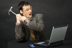 Furious young man breaks hammer computer Royalty Free Stock Photography