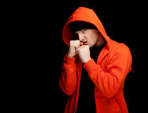 Furious young man in orange sweatshirt. Standing furious young man in orange sweatshirt with hood and black cap, with raised arm, black background Stock Photos