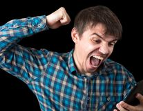The furious young man screams and waved his hand at the phone or tablet. Bad device. royalty free stock photos