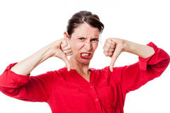 Furious young woman with disappointed thumbs down grinding teeth. For childish frustration, isolated over white background studio Royalty Free Stock Photo